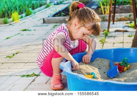 little girl playing in a sandbox in the yard on a summer day