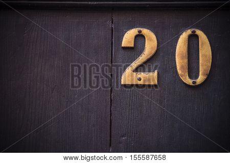 Metal number twenty with large dark wooden background