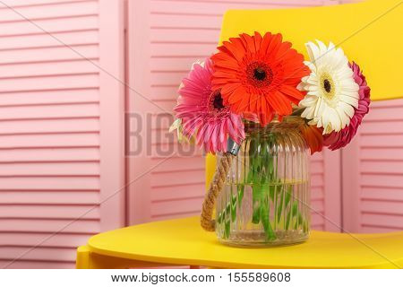 Vase with gerbera flowers on yellow chair against pink folding screen