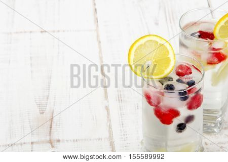 mineral water with fruit frozen in ice cubes