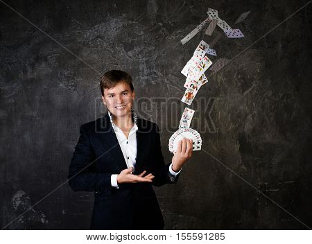 Illusionist man with fountain of cards on a dark background.