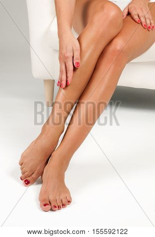 Spa and Epilation. Long woman legs after depilation on white background. Skin care.