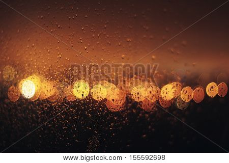 city blurring lights abstract circular bokeh on dark orange background with drops on glas