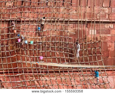 Jaipur, Rajasthan, India - July 21, 2011: Workers on wooden scaffold painting and renovate building of Amber Fort. UNESCO World Heritage Site as part of the group Hill Forts of Rajasthan.