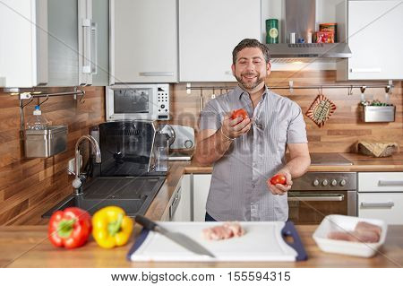 Man Juggling With Tomatoes In His Kitchen Laughing