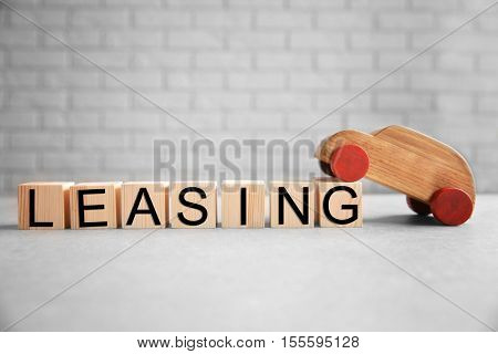 Cubes with word LEASING and toy car on brick wall background
