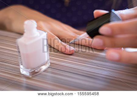 woman paints the nails of the fingers white lacquered