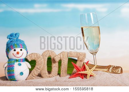 Figures 2017, a bottle of champagne and glass, snowman, starfish in the sand against the sea.