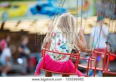 Cute little girl enjoing time at fun fair, chain swing ride, amusement park in summer. Rear view.