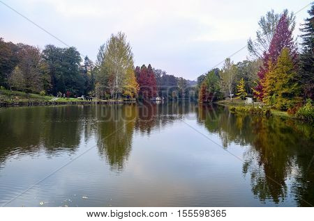 Istanbul Turkey - November 03 2013: Ataturk Arboretum is an arboretum in Bahcekoy Sariyer Istanbul Province. Autumn trees around lake. Fall trees reflected in lake. Autumnal scene with yellow orange and red leaves on trees.