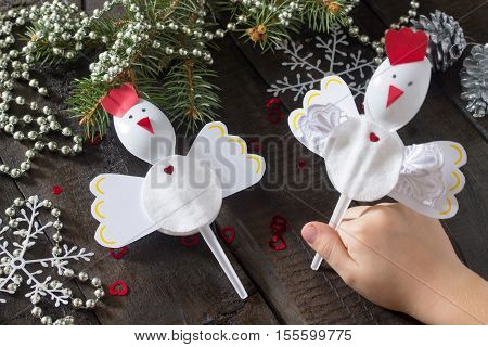 Child Cockerel Create A Christmas Gift Toy Of Christmas Toys. Glue, Scissors, Paper, Plastic Spoons