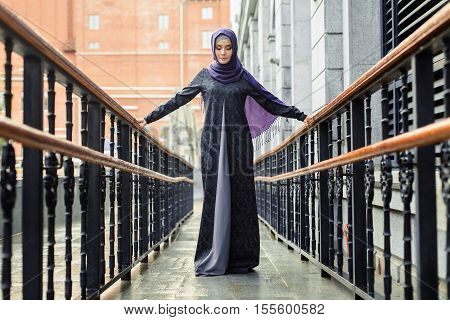 Islamic beautiful woman in a Muslim dress standing on a European street Ufa
