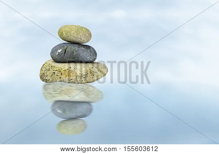 View of three stones floating on a cloudy background with the stones reflected in the foreground.