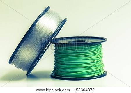Filament for 3D Printer crystal clear and bright green against bright background.