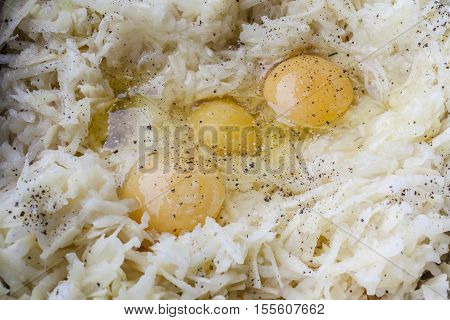 Grated potato and three eggs with seasoning for latkes in metal bowl from above closeup