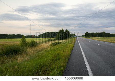 Country asphalt road through fields. Rain clouds on the sky. Forest on the backward. Long straight countryside road. Асфальтированная длинная дорога через поле.