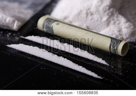 Rolled Hundred Dollars Banknote, Two Lines And Plastic Packet Of Cocaine On Black Background