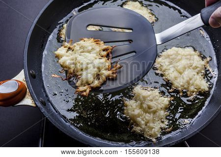 Turning over frying latkes with spatula in deep oil on pan from above