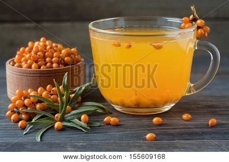 Tea of sea-buckthorn berries with honey and a branch on a wooden background.