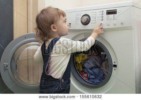 little girl starts washing machine in the bathroom