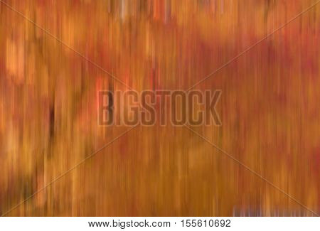 Blur of natural leaf colors in the Fall specifically oranges reds and yellows. Suitable for background or abstract.