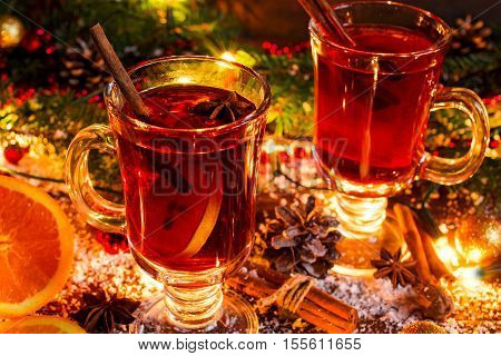 Two glasses of hot mulled wine with oranges and spices in christmas lights on wooden background covered with snow
