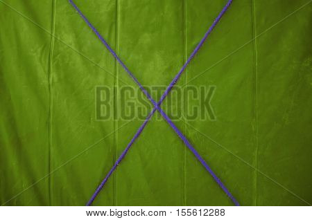 Texture green tarp with a purple cross in the middle of the rope. Yellow background.