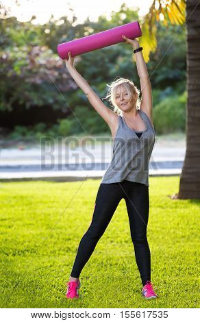 Young Beautiful Fitness Girl With Ponytail Holding Pink Mat And Ready For Doing Exercises
