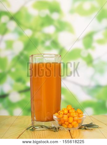 A glass of juice and a bowl of sea-buckthorn berries on a green abstract background.