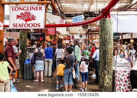 VANCOUVER CANADA - JULY 26: Visitors at the popular Granville Island Public Market July 26 2010 in Vancouver Canada. It's home to over 150 vendors offering fresh seafood meats sweets a variety of artisan cottage-industry foods and handmade crafts.
