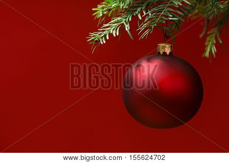 Red Christmas ornament hanging with copy space to the left. red background