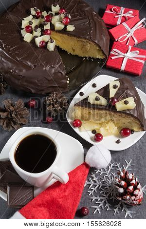 Homemade chocolate-glazed pineapple cake with one slice on white plate and a cup of coffee with three pieces of chocolate on grey background with christmas decorations