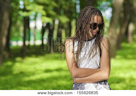 Teenagers Lifestyle Concepts. Young African American Teenager Girl With Plenty of Long Dreadlocks Posing in Sunglasses Outdoors. Horizontal Composition