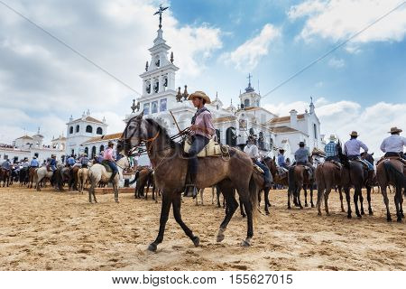 El ROCIO, ANDALUCIA, SPAIN - 26 JUNE 2016: Young boy rider guides horse to be baptized. Facing the Church.