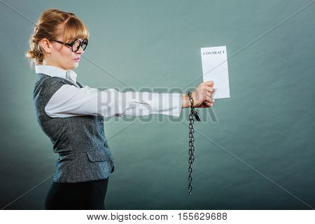 Business concept. Serious woman businesswoman with chained hands holding contract side view grungy background