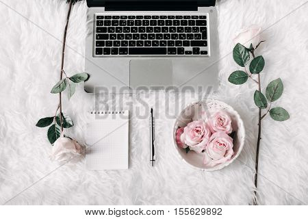 Freelance woman workspace in flat lay style with laptop, vintage tray, roses, notebook and pen on white fur background. Top view, flat lay. Freelance concept. poster