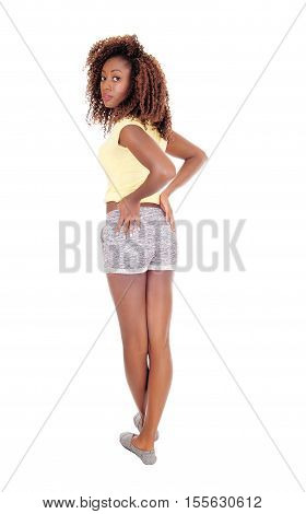 A beautiful young African American woman in shorts standing from the back isolated for white background.