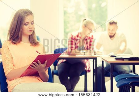 Education high school teamwork and people concept - student girl with notebook sitting in front of students her group mates in classroom