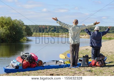 Two guys admire the scenery raised his hands to the sky in delight. Inflatable kayak loaded tourist equipment moored to the bank of the pond.