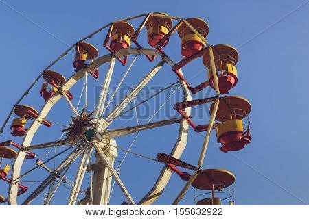 Closeup of a big ferris wheel with red and yellow colored cabins and white axis and spokes over blue clear sky.
