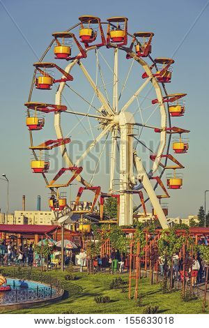 Bucharest Romania - May 19 2014: People have fun relax or enjoy a ride in a giant colorful ferris wheel in Tineretului Park a large amusement public park created in 1965 in southern Bucharest.