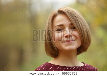 Closeup portrait of smiling woman with natural makeup and fashionable haircut on blurred nature background
