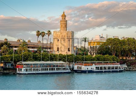 View of Golden Tower, Torre del Oro, of Seville, Andalusia, Spain over river Guadalquivir at sunset. Beautiful sunset view.