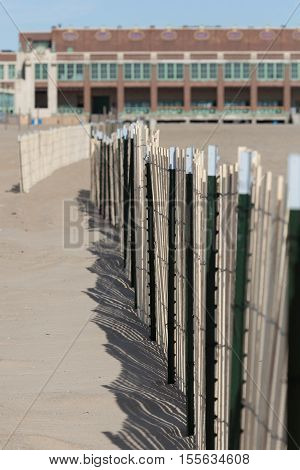 A view of a sand fence on the beach in Asbury Park New Jersey. The famous Convention Hall is visable in the background.