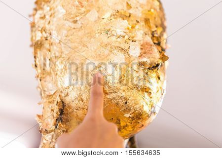 Women Hand Putting Gold Leaf Onto The Buddha Statue To Gild. Which People Use To Worship The Buddha