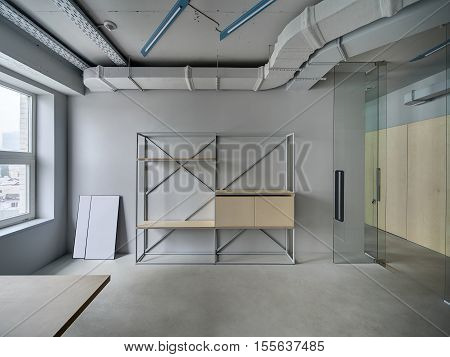 Business room in a loft style with gray walls. There is a window, a metal stand with the wooden shelves and lockers, a glass partition with a glass open door. Horizontal.
