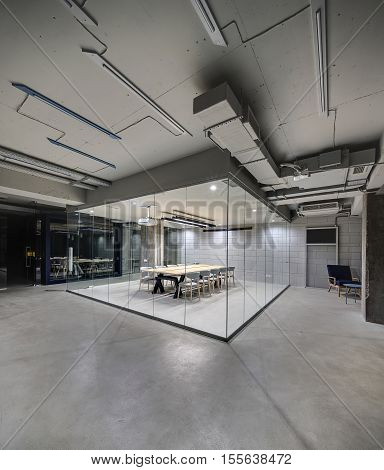 Office in a loft style with glowing lamps, light brick walls and concrete columns. There is a meeting zone with a large wooden table with gray chairs and glass partitions. Vertical.