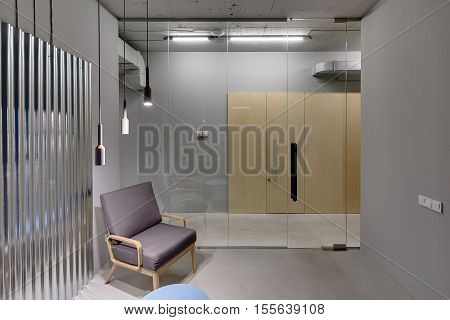 Office interior in a loft style with gray walls. There is a room with a glass partition with door, an armchair, a small table and a metal panel on the wall. Opposite the room there are wooden doors.