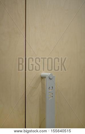 Closeup photo of the door handle. On the handle there is an inscription WC. Door is wooden. Vertical.