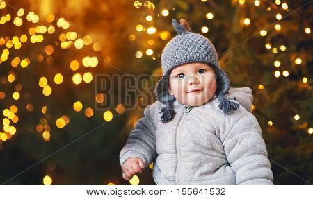The first Christmas and New Year! Portrait of a cute baby child on New Year's or Christmas background: Christmas tree with illuminated garlands.